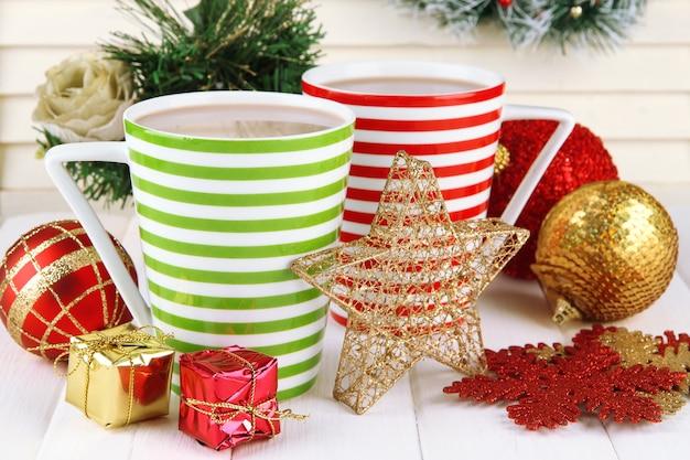 Kubki gorącego kakao z dekoracjami świątecznymi na stole na drewnianej ścianie