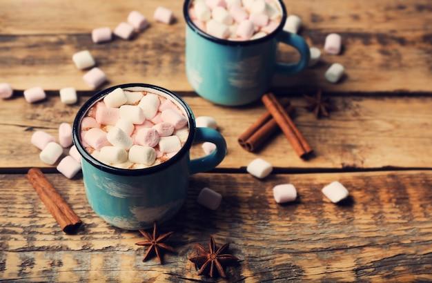 Kubki gorącego kakao z piankami na stole