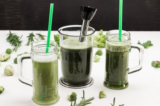 Kubki i blender z zielonymi koktajlami warzywnymi. zielone słomki w kubkach.