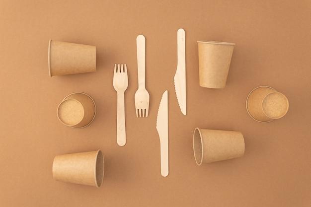 Kubki papierowe jednorazowe z drewnianymi widelcami i nożami w kolorze beżowym