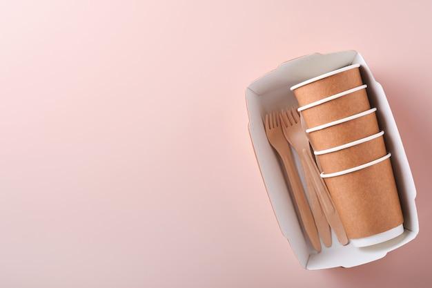 Kubki papierowe, naczynia, torba, drewniane widelce, słomki do picia, pojemniki na fast food, drewniane sztućce na różowym tle. zastawa stołowa z ekologicznego papieru rzemieślniczego. koncepcja recyklingu i dostawy żywności. makieta. widok z góry
