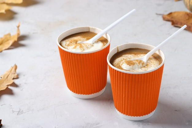 Kubki papierowe z pyszną latte z dyni i przyprawami na szarym stole. zbliżenie. format poziomy