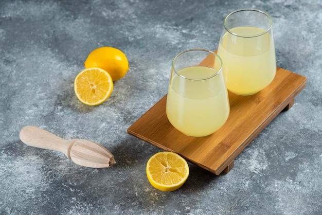 Kubki pełne lemoniady z plasterkami cytryny i drewnianym rozwiertakiem.