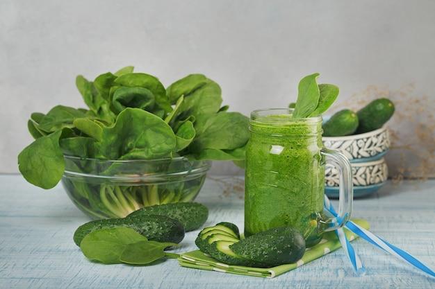 Kubki słoika wypełnione świeżym zielonym koktajlem ze szpinaku i ogórka na jasnoniebieskim drewnianym tle. zdrowa żywność i koncepcja wegetariańska.