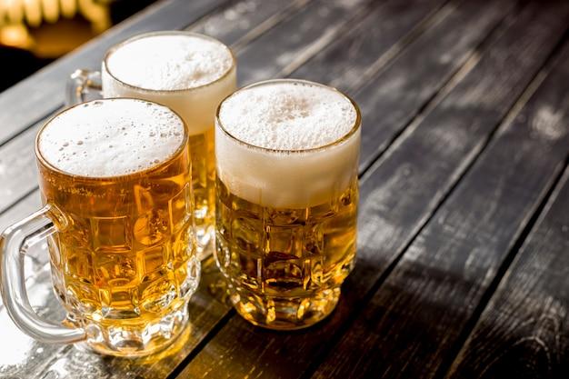 Kubki świeżego spienionego piwa na stole barowym.