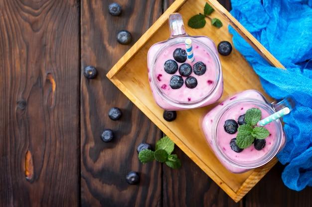 Kubki z masonem ze świeżymi koktajlami jagodowymi jagodami pojęcie i zdrowie lub detoksykacja