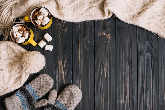 Kubki z piankami w pobliżu ciepłej odzieży