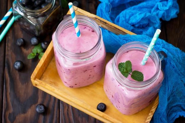 Kubki ze słoiczków ze świeżymi koktajlami jagodowymi jagodami koncepcja prawidłowego odżywiania