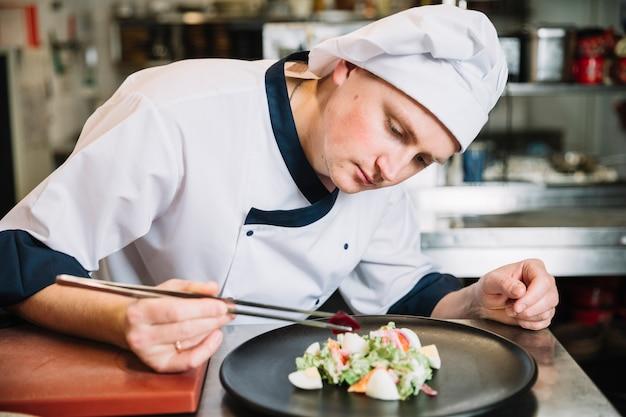 Kucbarski kładzenia warzywo na talerzu z sałatką