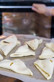 Kucharz kobieta kładzie chrupki serowe na blasze do pieczenia w piekarniku. świeże wypieki w kawiarni