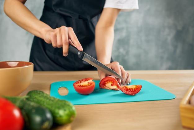 Kucharz kobieta w kuchni do krojenia warzyw na białym tle