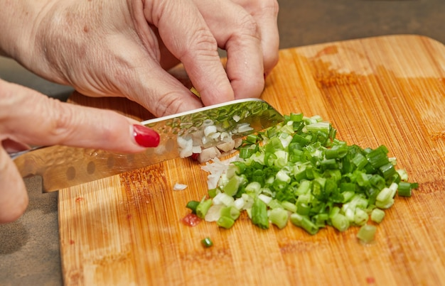 Kucharz kroi przepis zieloną cebulę na drewnianej desce w kuchni.