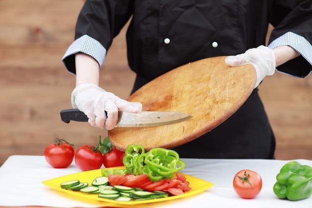 Kucharz kroi świeże warzywa z farmy na obiad na stole