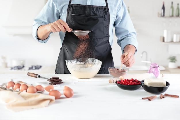 Kucharz na rustykalnej kuchni. męskie dłonie ze składnikami do gotowania produktów mącznych lub ciasta, chleb, babeczki, ciasto, ciasto, pizza
