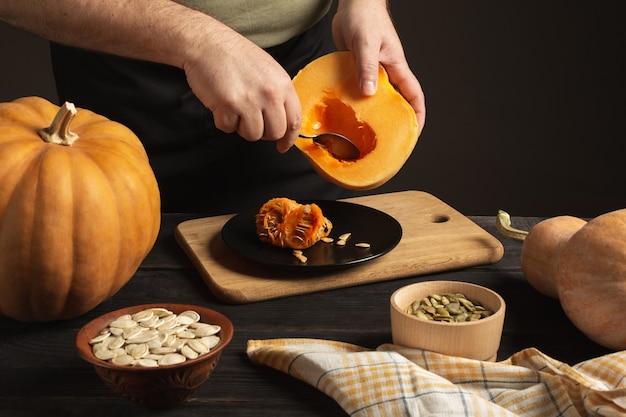 Kucharz oddziela ziarno od dyni przekrojonej na pół. na czarnym drewnianym stole są całe dynie różnych rozmiarów. nasiona w dwóch miseczkach.