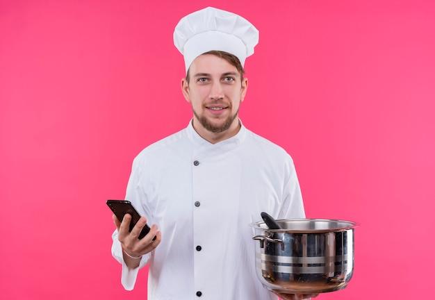 Kucharz patrząc na aparat uśmiech na twarzy z telefonem i patelnią pod ręką stojącą na różowej ścianie
