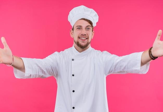 Kucharz patrząc na aparat uśmiech w twarz robi gest przytulenia stojąc nad różową ścianą