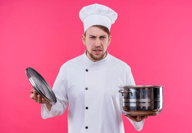 Kucharz patrząc na aparat wściekły na twarzy z patelnią na dłoni stojącej nad różową ścianą