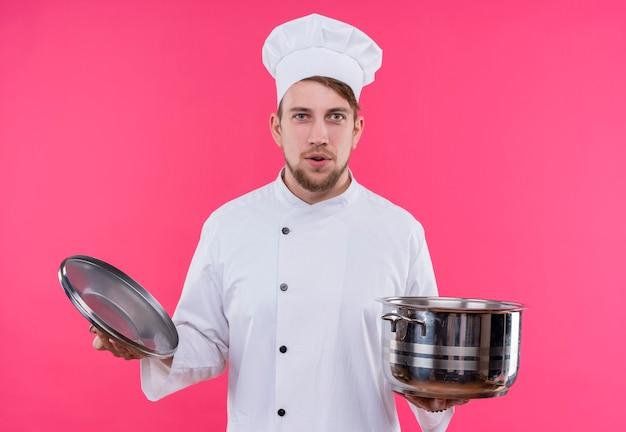 Kucharz patrząc na aparat wychodzący na twarz z patelnią stojącą nad różową ścianą