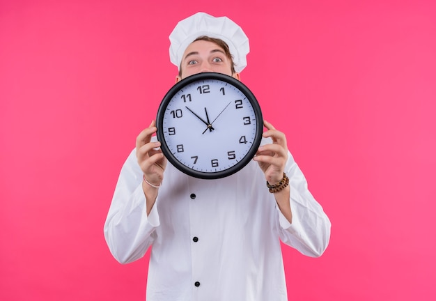 Kucharz patrząc na niespodziankę kamery na twarzy pokazującej zegar stojący nad różową ścianą