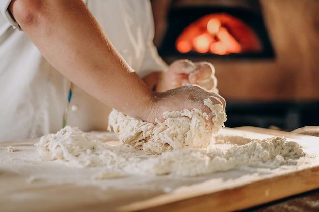 Kucharz przygotowuje ciasto do pizzy. gotowanie. mężczyzna ugniata rękami ciasto do robienia pizzy w piekarniku.