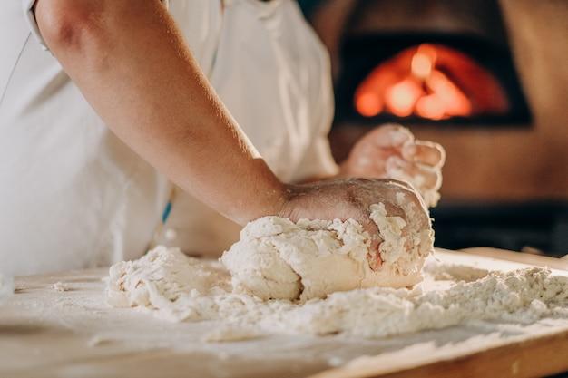 Kucharz przygotowuje ciasto do pizzy. mężczyzna ugniata rękami ciasto do robienia pizzy w piekarniku.