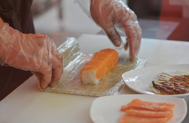Kucharz przygotowuje sushi obracając bułkę zbliżenie ręki kucharza przygotowującego sushi