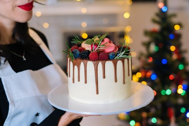 Kucharz trzyma domowe ciasto świąteczne z owocami. szczęśliwego nowego roku i wesołych świąt