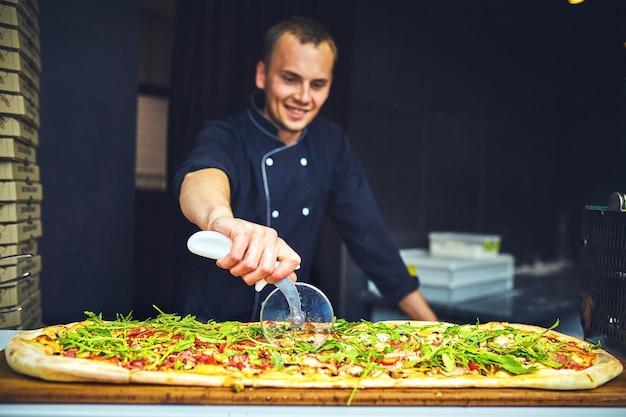 Kucharz trzyma dużą pizzę.