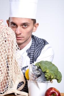 Kucharz, trzymając w rękach bawełniany worek ekologiczny. ryba, cytryna i brokuły w wiaderku na drewnianym stole z czerwonym jabłkiem, siatkowa torba wielokrotnego użytku. pojęcie ekologii