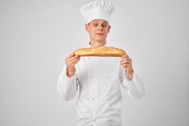 Kucharz w mundurze szefa kuchni trzyma bochenek bagietki