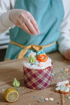 Kucharz w rękawiczce rzuca słodkie okruchy na polewę wielkanocnego ciasta