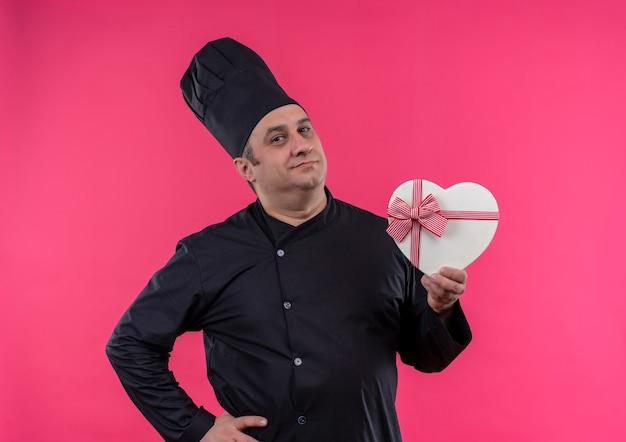 Kucharz w średnim wieku w mundurze szefa kuchni, trzymając pudełko w kształcie serca, położył rękę na biodrze na odizolowanej różowej ścianie