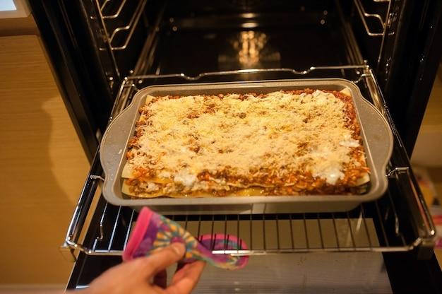 Kucharz wkłada naczynie do piekarnika do pieczenia. zostajemy w domu i gotujemy lasagne.