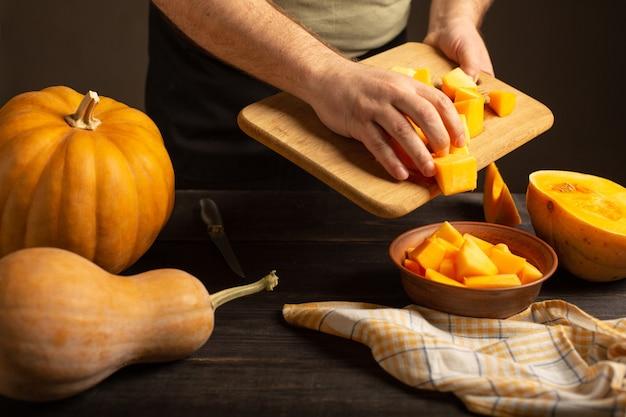 Kucharz wrzuca plasterki dyni z deski do krojenia do głębokiej miski.