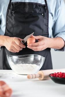 Kucharz z jajkami w rustykalnej kuchni na tle męskich dłoni