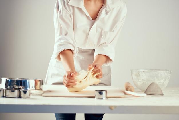 Kucharz zwija ciasto z mąki w kuchni