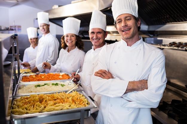 Kucharze stojący przy serwowaniu tac makaronu