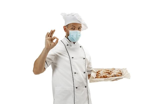 Kuchenka, kucharz, piekarz w masce na twarz w mundurze na białym tle z rogalikami. młody mężczyzna, portret kucharza restauracji. biznes, podwórko, zawód zawodowy, koncepcja emocje. miejsce na reklamę.