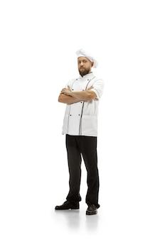 Kuchenka, kucharz, piekarz w mundurze na białym tle na tle białego studia, smakosz. młody człowiek, portret kucharza restauracji. biznes, podłoga, zawód zawodowy, koncepcja emocji. copyspace dla reklamy.