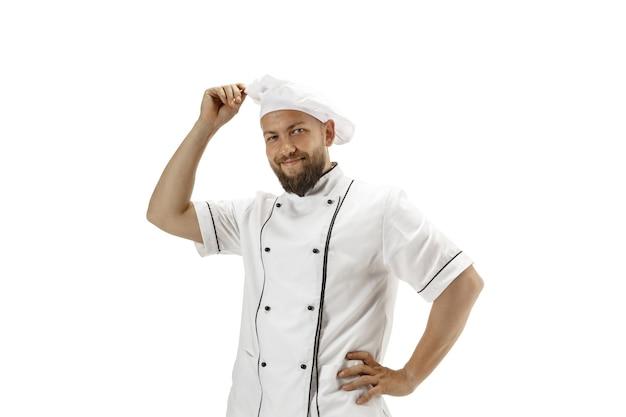 Kuchenka, kucharz, piekarz w mundurze na białym tle na tle białego studia, smakosz. młody mężczyzna, portret kucharza restauracji. biznes, podwórko, zawód zawodowy, koncepcja emocje. miejsce na reklamę.