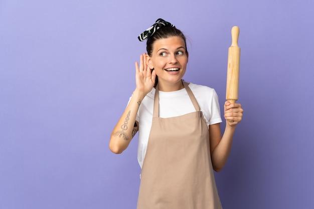 Kuchenka słowacka kobieta na białym tle na fioletowej ścianie słuchając czegoś, kładąc rękę na uchu