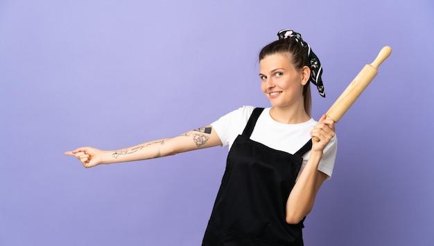 Kuchenka słowacka kobieta na białym tle na fioletowej ścianie wskazując palcem w bok i prezentuje produkt
