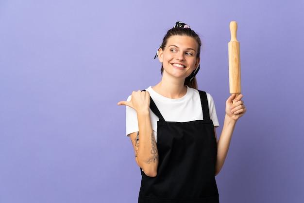 Kuchenka słowacka kobieta na białym tle na fioletowej ścianie, wskazując w bok, aby przedstawić produkt