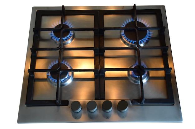 Kuchenna kuchenka gazowa z czterema palnikami płonącymi niebieskim płomieniem na białym tle ze ścieżką przycinającą