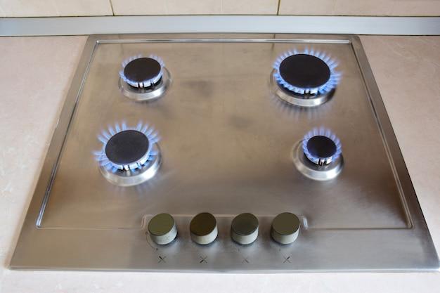 Kuchenna kuchenka gazowa z czterema rozpalonymi do czerwoności palnikami spalającymi niebieski płomień