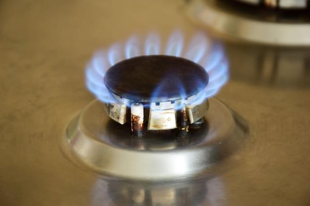 Kuchenna kuchenka gazowa z palącym się gorącym niebieskim płomieniem palnika
