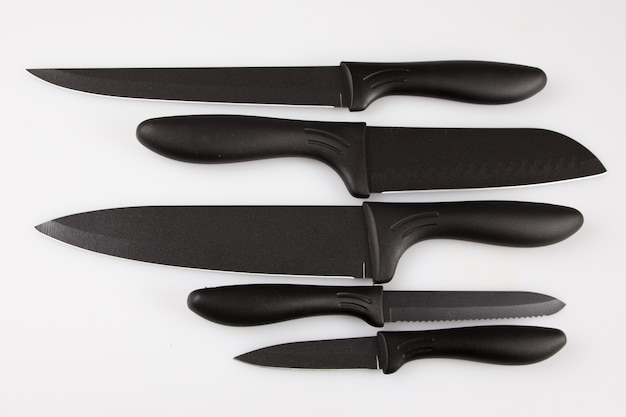 Kuchenne czarne noże ustawiają odosobnionego przeciw białemu tłu