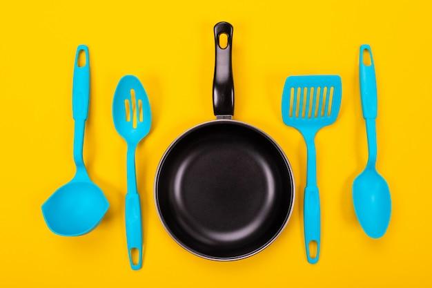 Kuchenni naczynia dla gotować w kuchni odizolowywającej z copyspace na kolorze żółtym