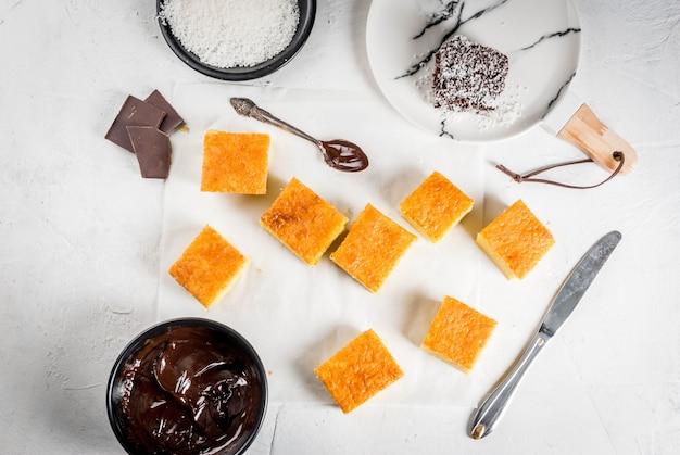 Kuchnia australijska. przygotowanie tradycyjnego australijskiego deseru lamington: herbatnik w czekoladzie z kokosowym proszkiem do golenia. widok z góry. biały stół.
